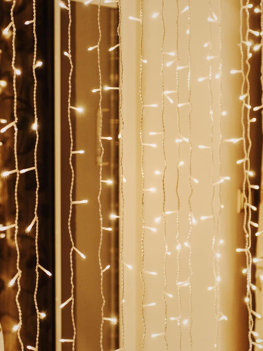 Sznury ze światełkami na tło za parą młodą